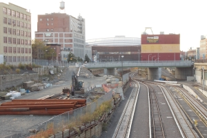 Looking west from Vanderbilt Avenue at the two-block-long railyard, with Carlton Avenue in the mid-range and the arena in the background. The Storage Mart building at right would be demolished before construction over the railyard, while the yellow building at left, currently on the block that features the above-ground arena parking lot, would be demolished. After building three towers around the arena, Forest City Ratner plans to build four on the parking lot block.